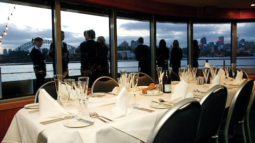 View of the dinning tables aboard a cruise ship with guests looking out the windows to the view of Sydney Harbour