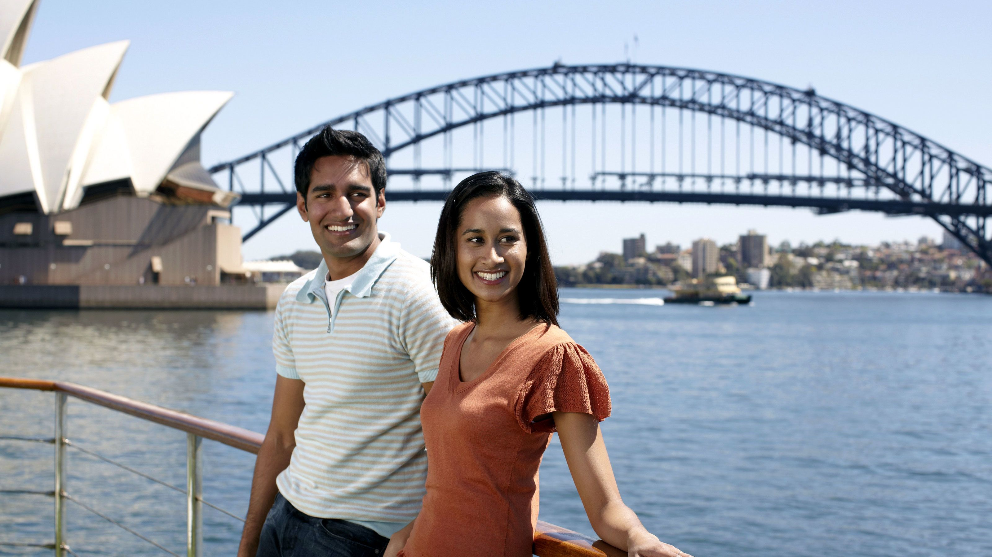 Smiling couple standing on the deck of a cruise ship looking out on the Sydney Harbour