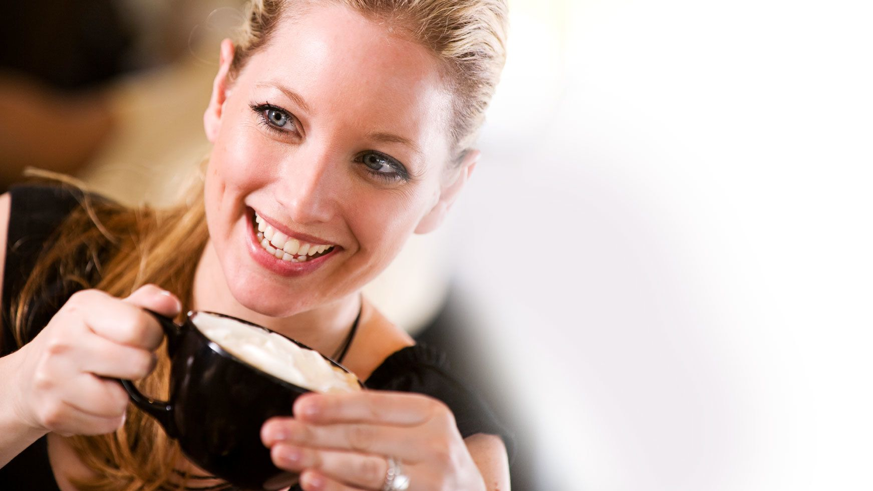 Smiling woman with a cup of coffee aboard a cruise ship on the waters of the Sydney Harbour