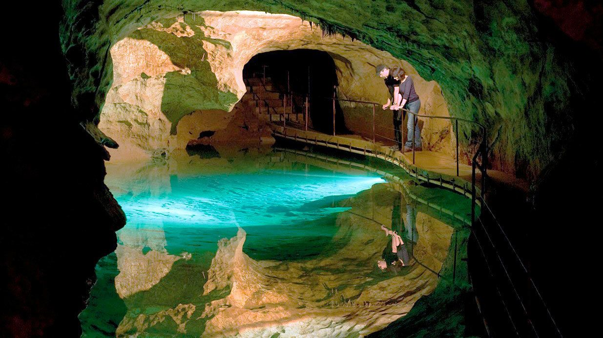 Couple viewing the waters inside the Jenolan Caves while their reflection is showing upon the waters