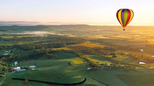 A hot air balloon floating over the lush green lands of the Hunter Valley wine region