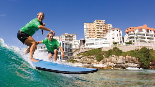 A man and woman enjoying themselves while they surf in the waters of Bondi Beach