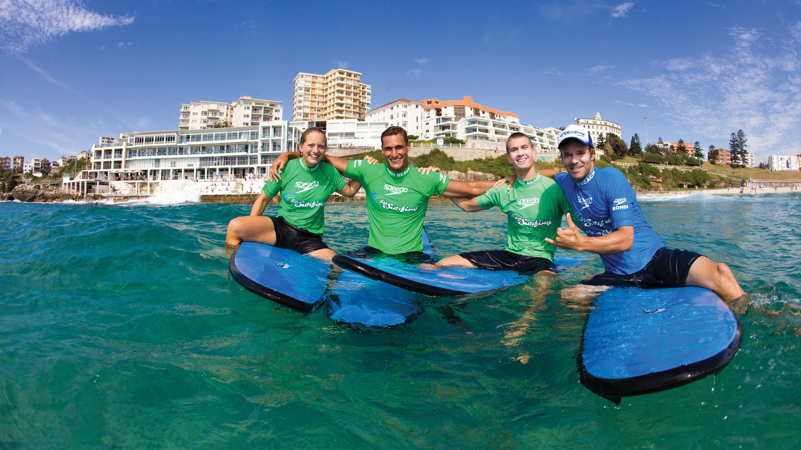 A group taking a photo as they sit on their surfboards on Bondi Beach