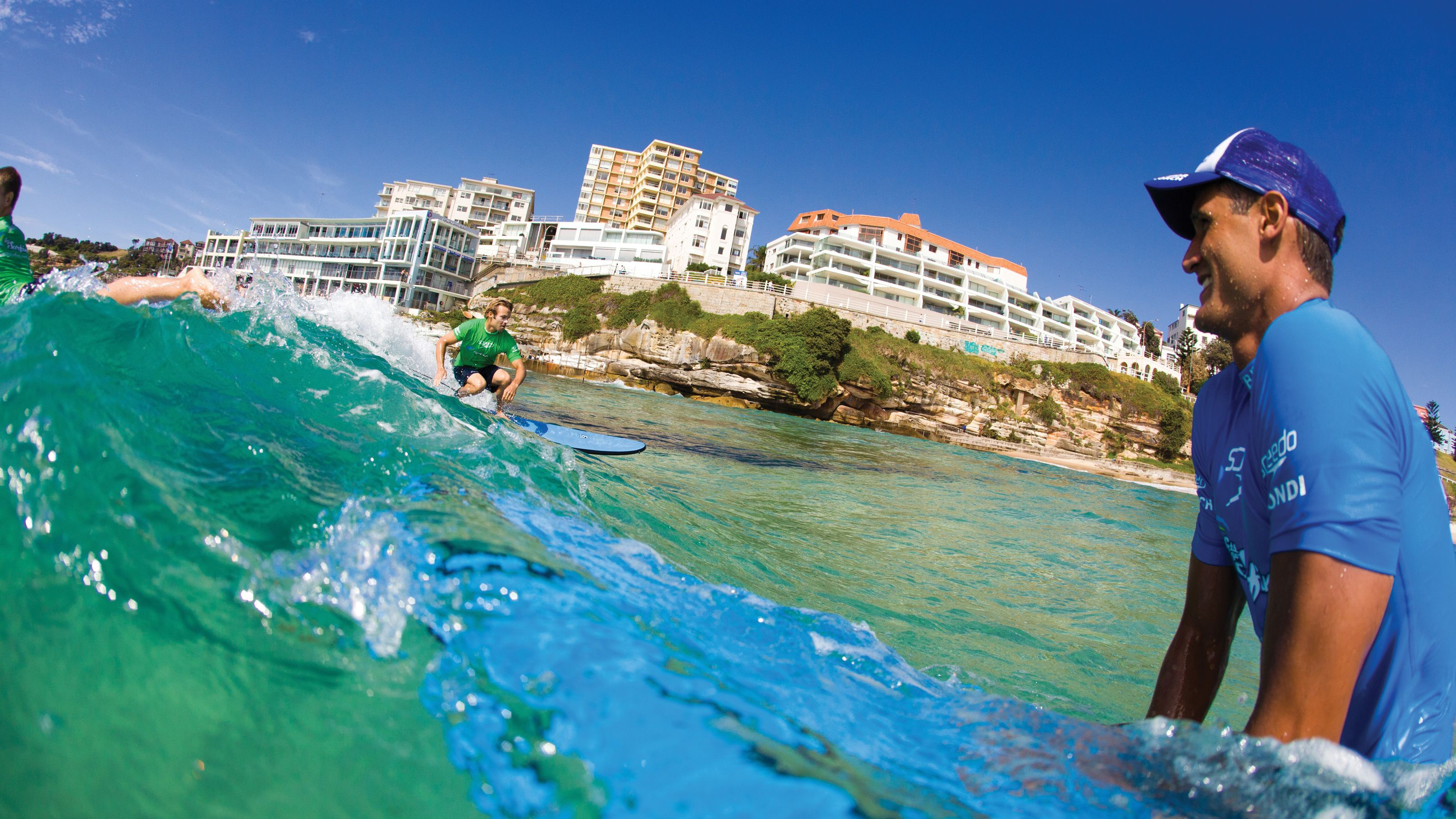 Surf instructor in the waters of Bondi Beach smiling as he watches out for those surfing