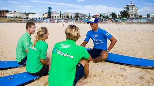 Group receiving instructions from the surf instructor as they sit on the sands of Bondi Beach on a sunny day