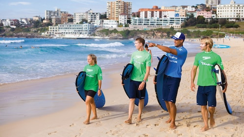 Group walking with their surf instructor while holding their surfboards on Bondi Beach