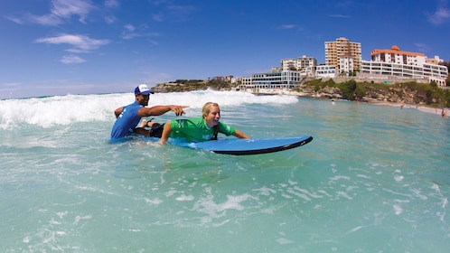 Instructor teaching a student how to surf in the waters of Bondi Beach