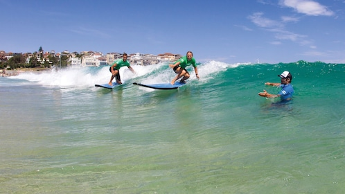 Surf instructor instructing two surfers on Bondi Beach