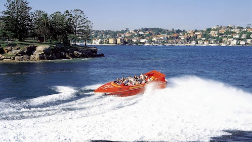 Wondrous view of a jet boat riding through the waters of the Sydney Harbor with the city in view in the background on a nice day