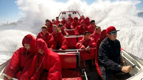 Close up view of guests aboard a red jet boat ride on the Sydney Harbour