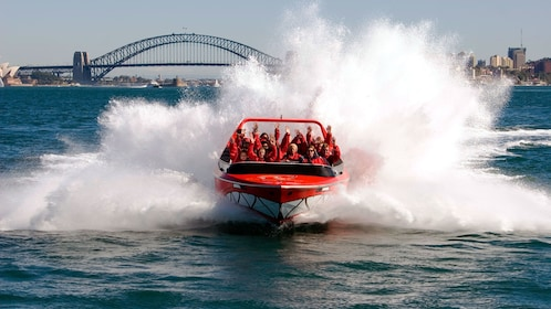A red jet boat ride making a splash on the Sydney Harbour with the cityscape viewable in the background