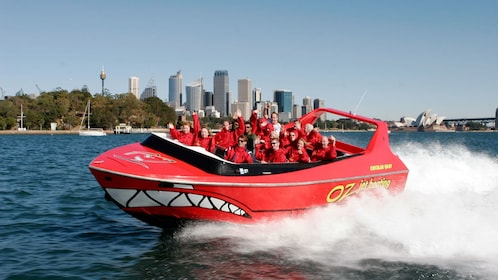 A red jet boat ride on the Sydney Harbour with the cityscape viewable in the background
