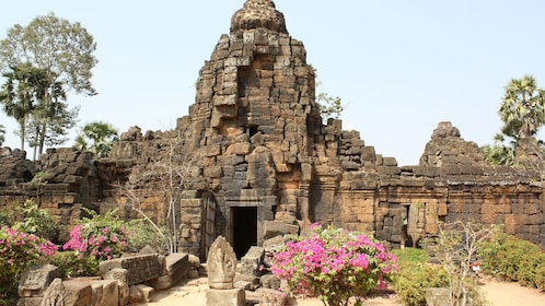 Flowers surround the remains of a temple in Cambodia