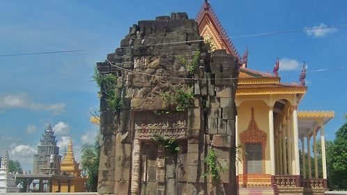 The remains of an ancient temple contrasted by a newer temple behind it in Cambodia