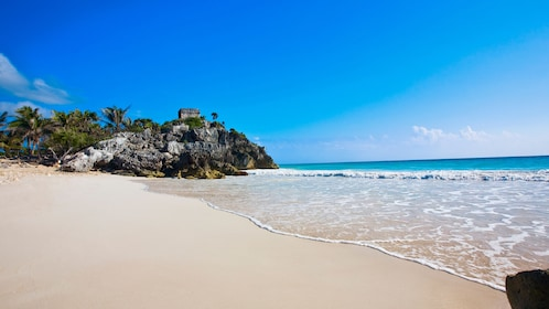 Sandy shore and bright blue water near Tulum