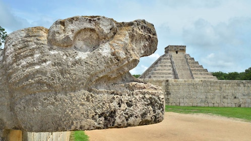 Jaguar head sculpture infront of he El Castillo pyramid at Chichen Itza