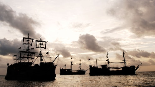 Pirate ships silhouetted at sunset