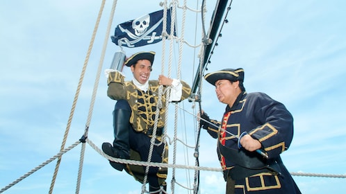 Two pirates dueling up in the rigging of a pirate ship