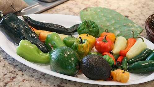 Plate with a variety of peppers, avocado, and other fresh local ingredients