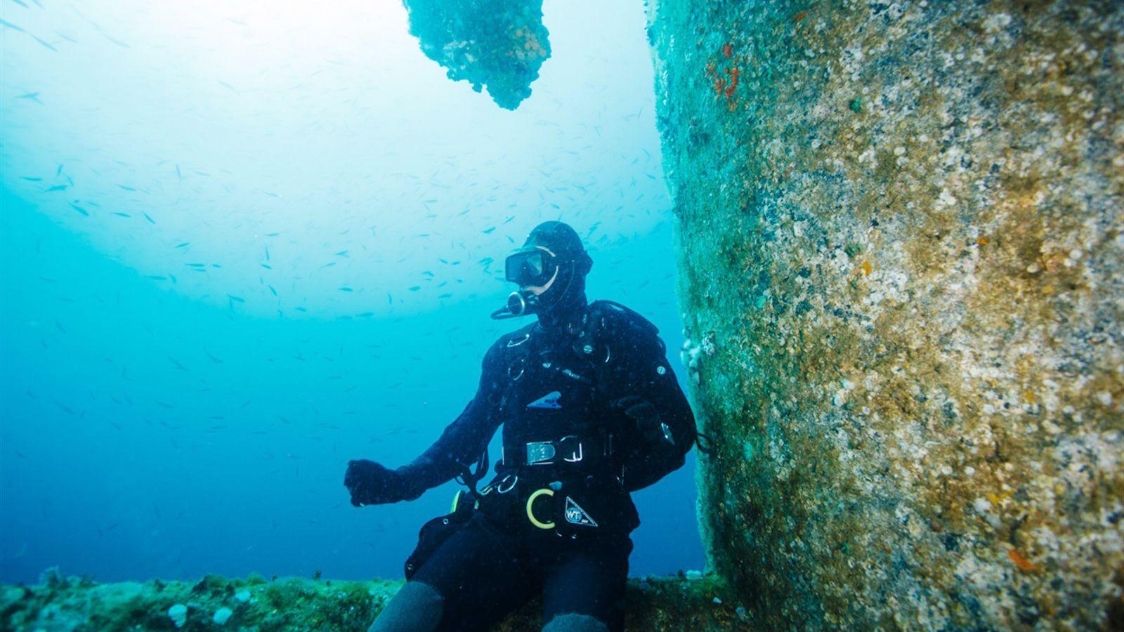 Scuba diver sitting on a sunken structure in Cancun