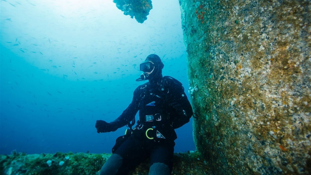 Show item 5 of 5. Scuba diver sitting on a sunken structure in Cancun