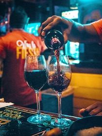 Bartender pouring wine into two glasses