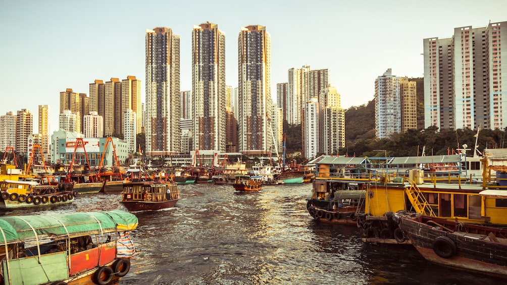 Show item 3 of 10. Tour boats and fishing boats at the docks in Hong Kong