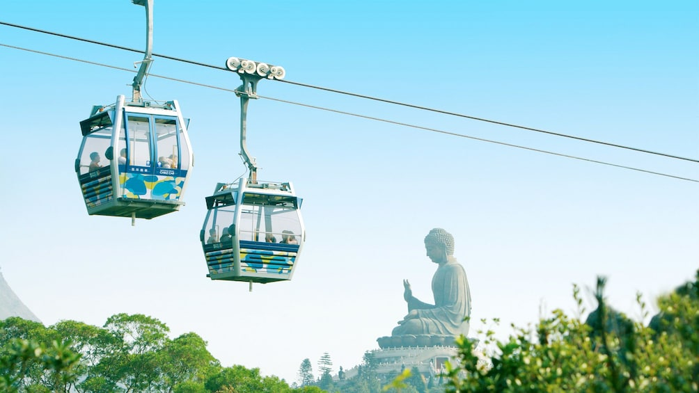 Show item 10 of 10. Gondolas passing each other as they travel over Lantau Island in Hong Kong
