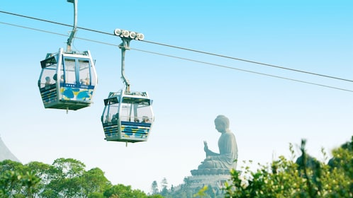 Gondolas passing each other as they travel over Lantau Island in Hong Kong