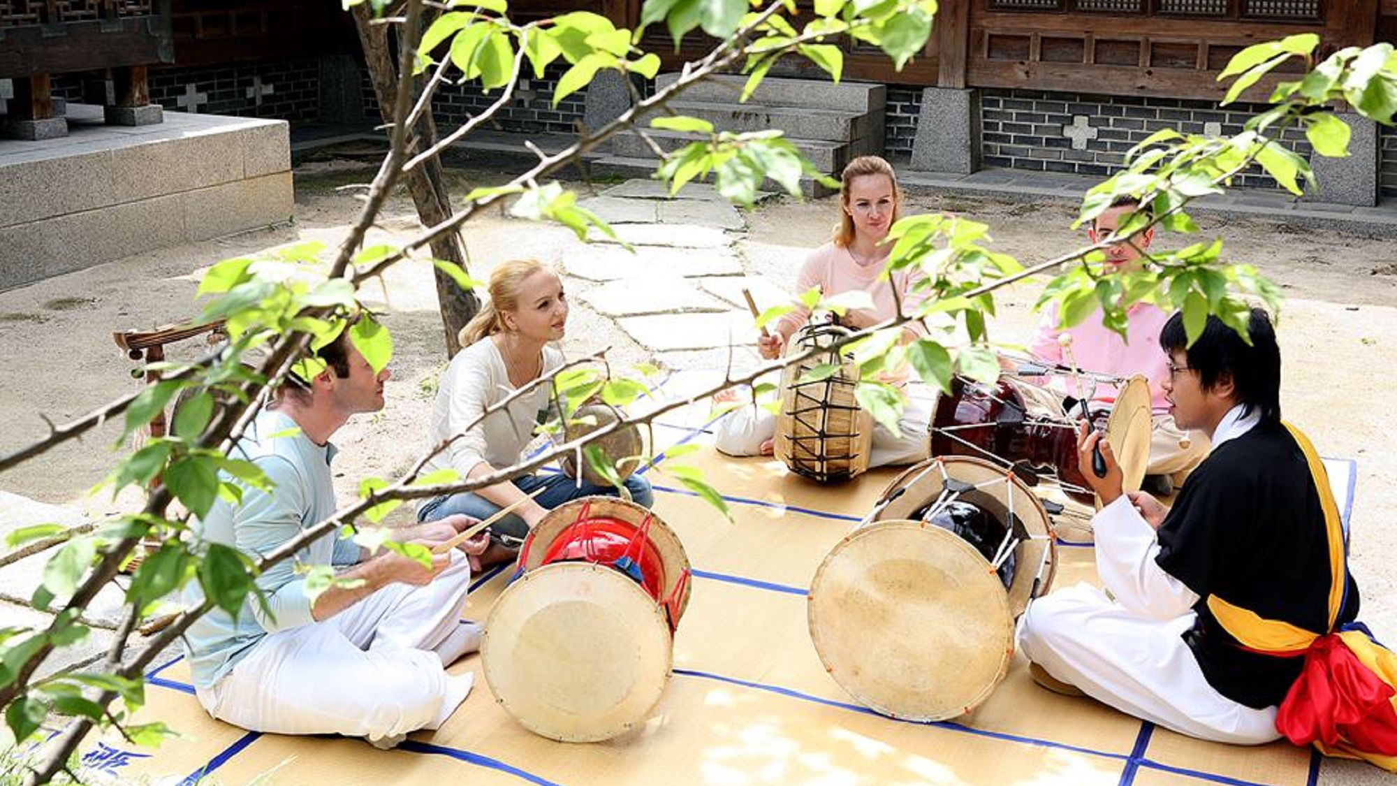 Tourists learning about Korean musical instruments at the Korea House in Seoul