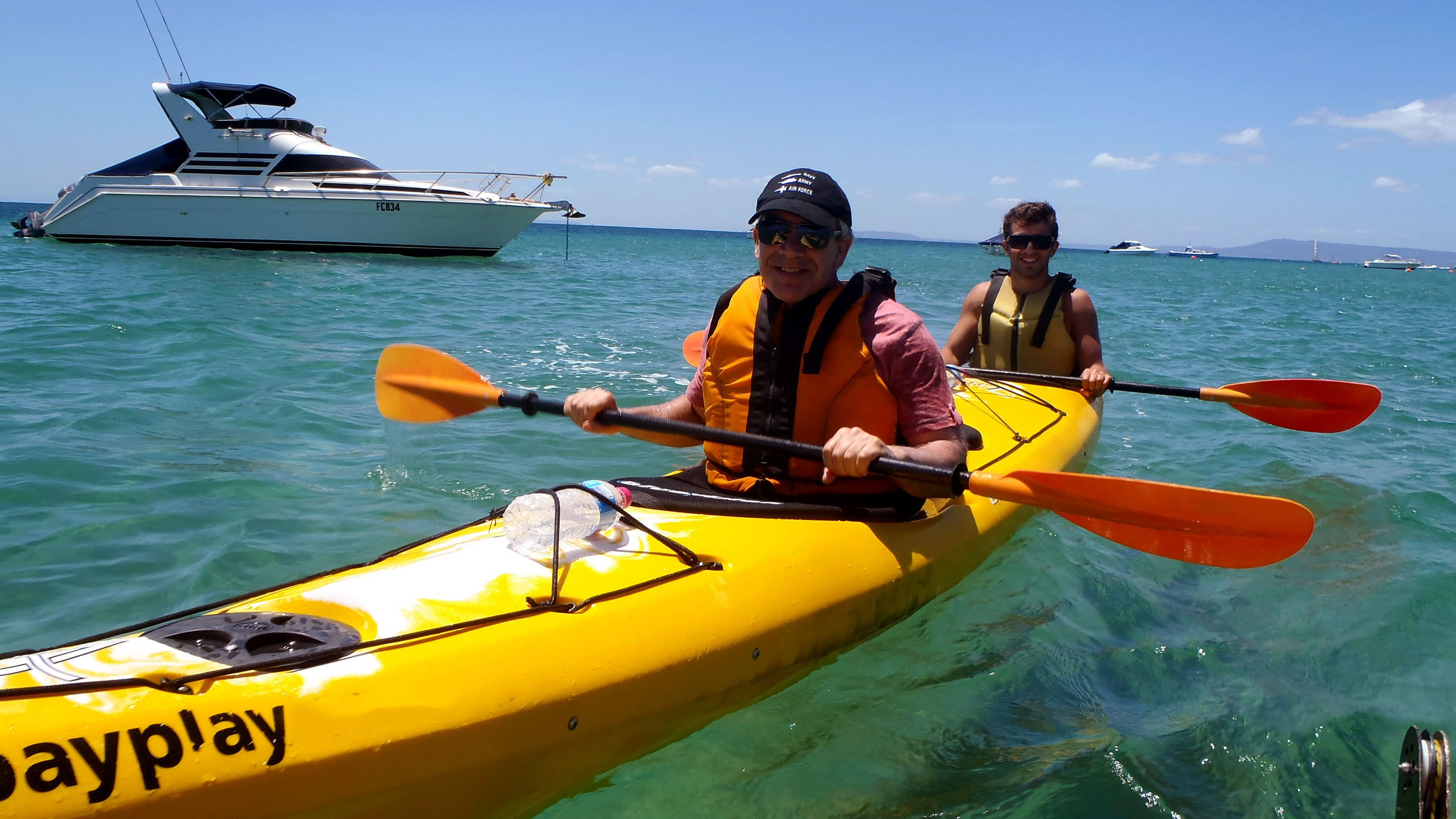 Two sea kayakers near a boat at Mornington Peninsula