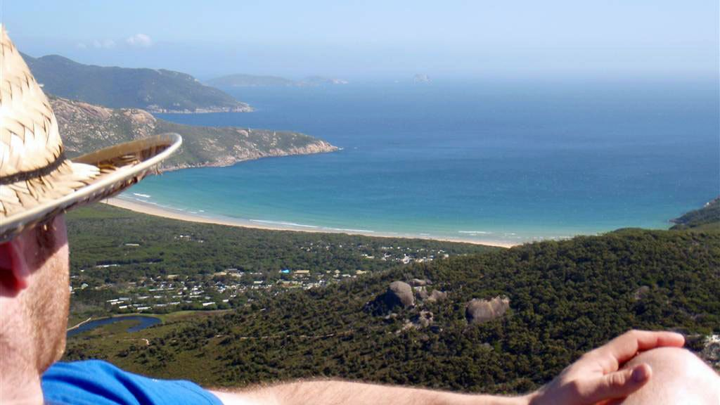 Man looking out at the town along the coast from Wilson Promontory National Park in Victoria, Australia