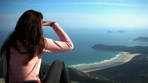 Woman looking out at the peninsula from a viewpoint at Wilson Promontory National Park in Victoria, Australia