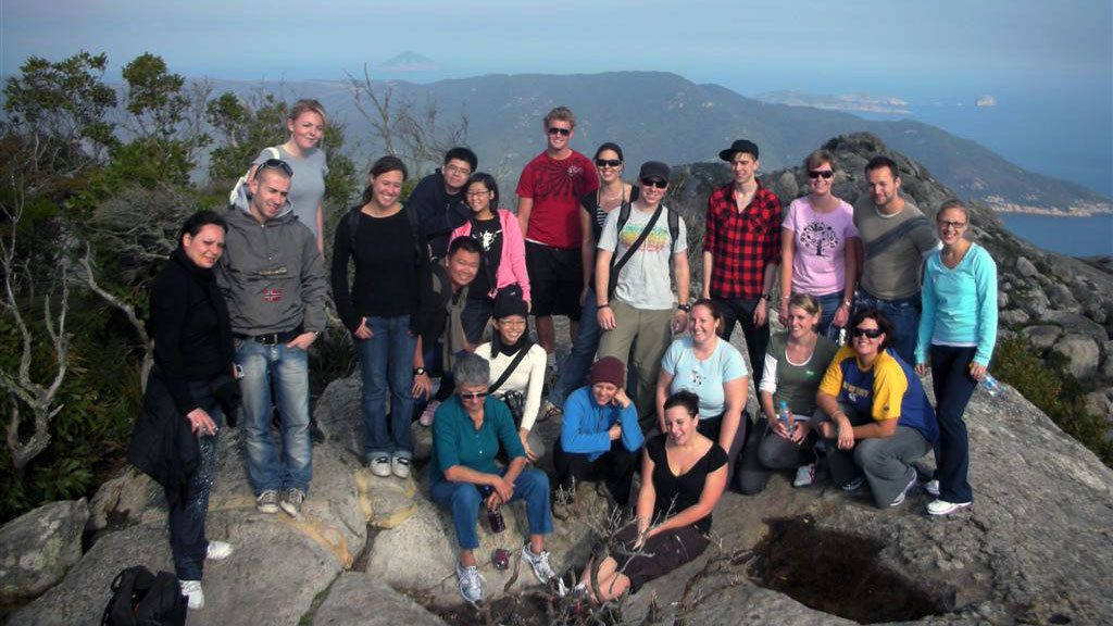 Tour group standing on a rock at a viewpoint at Wilson Promontory National Park in Victoria, Australia