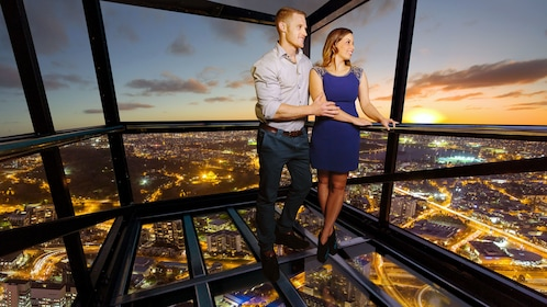 Couple in the glass cube of The Edge outside the Eureka Skydeck at sunset in Melbourne