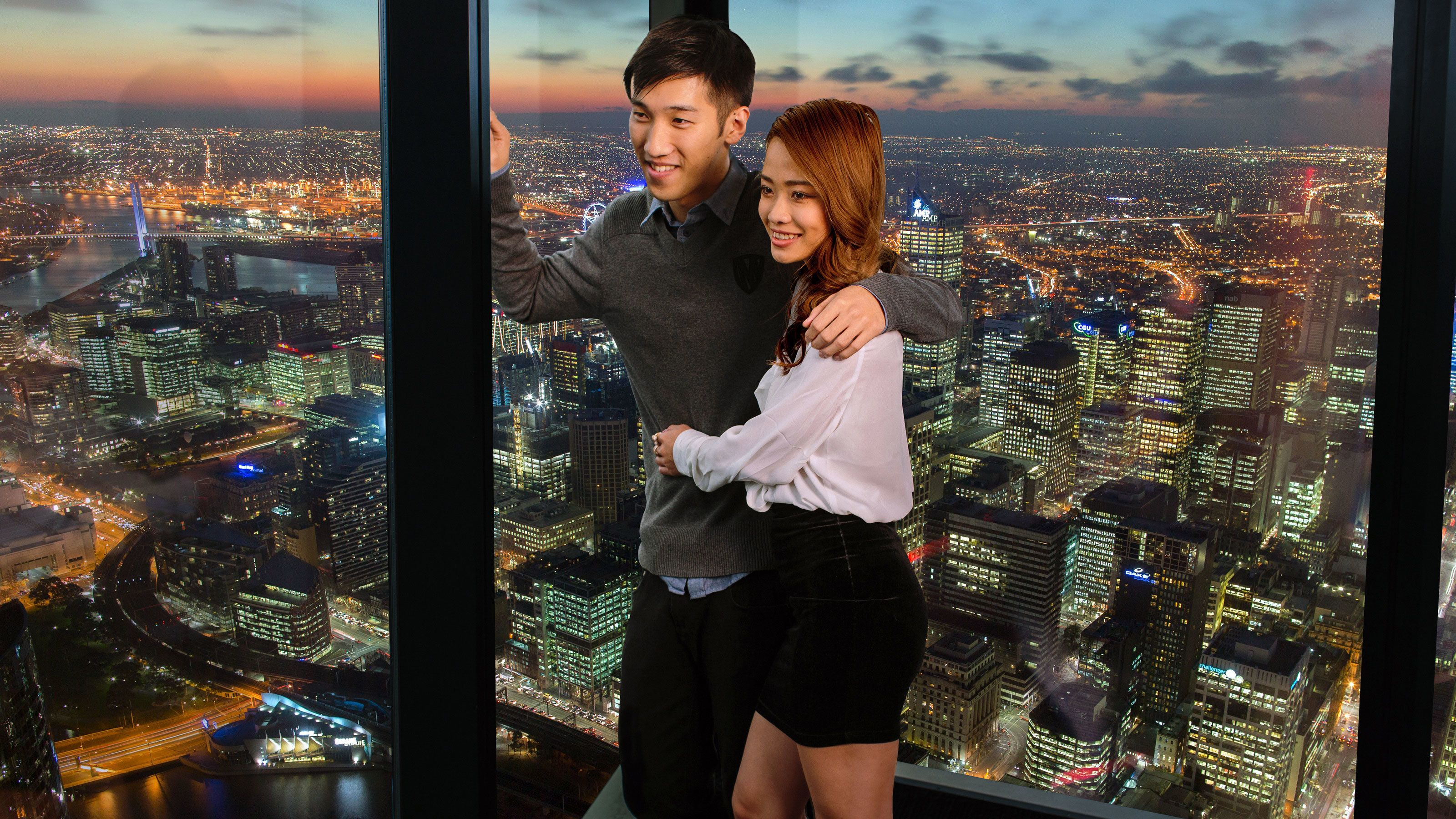 Couple leaning against the floor to ceiling windows of the Eureka Skydeck with the city in the background in Melbourne