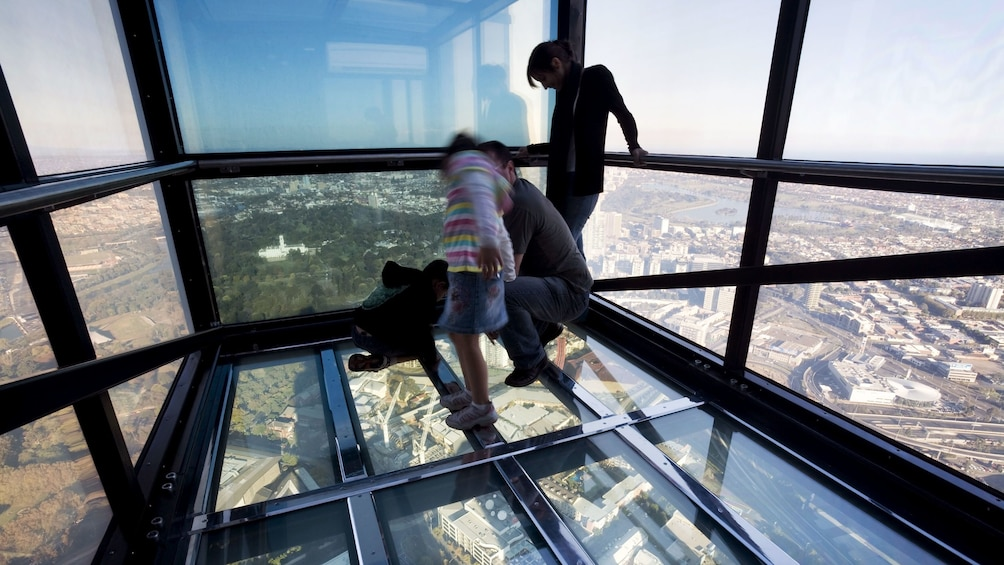 Show item 2 of 7. Family looking through the glass floor of the Edge outside the Eureka Skydeck high above the city in Melbourne