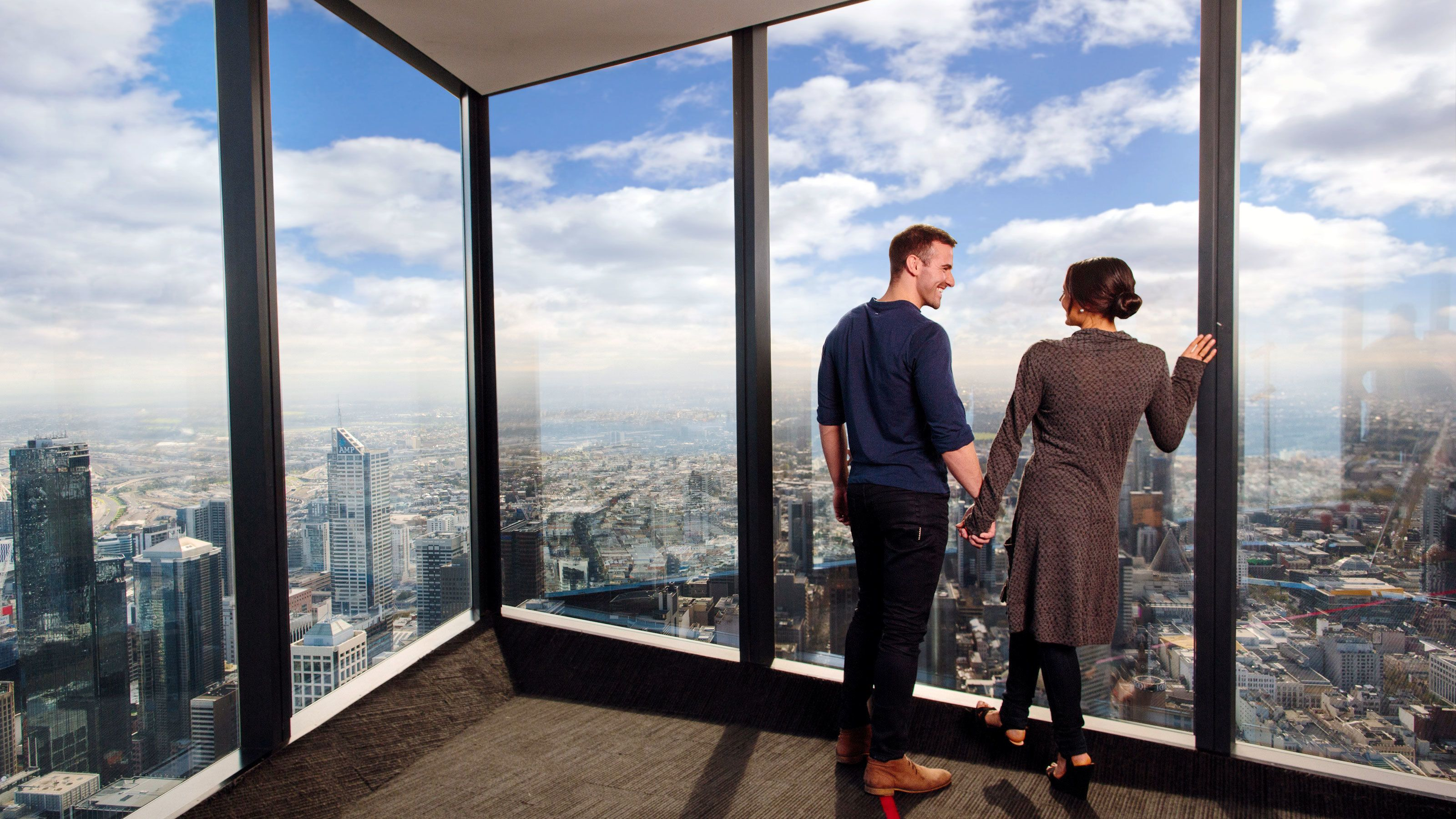 Couple looking out the large glass windows at the city from the Eureka Skydeck in Melbourne
