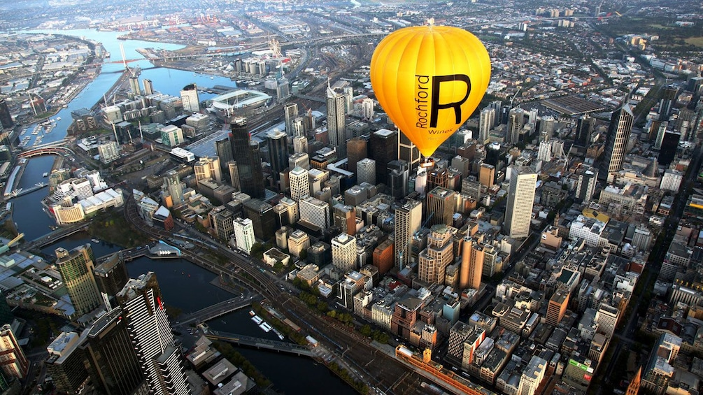 Hot air balloon flying over the skyscrapers of Melbournes