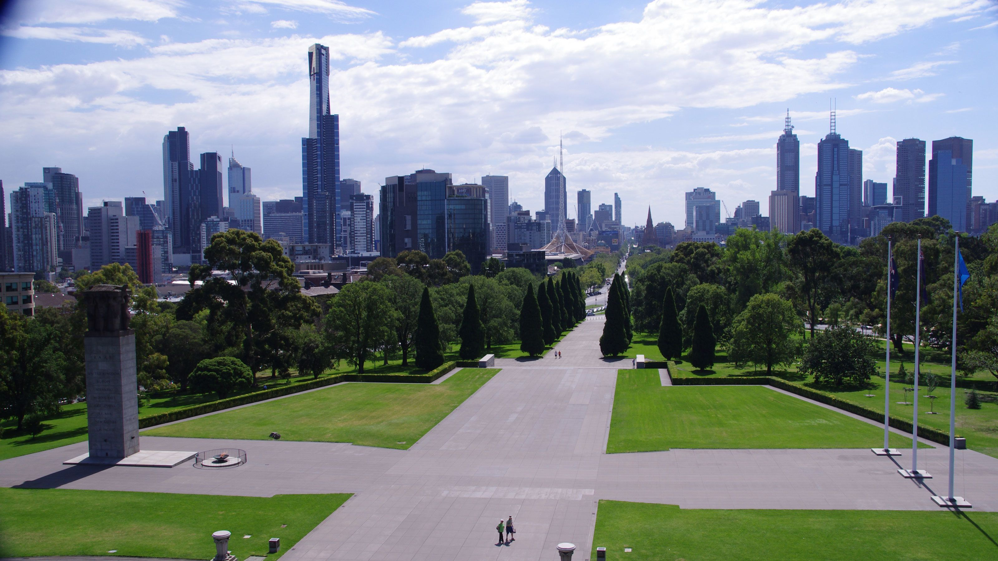 Paved walkways through the Royal Botanical Gardens with the city in the background in Melbourne