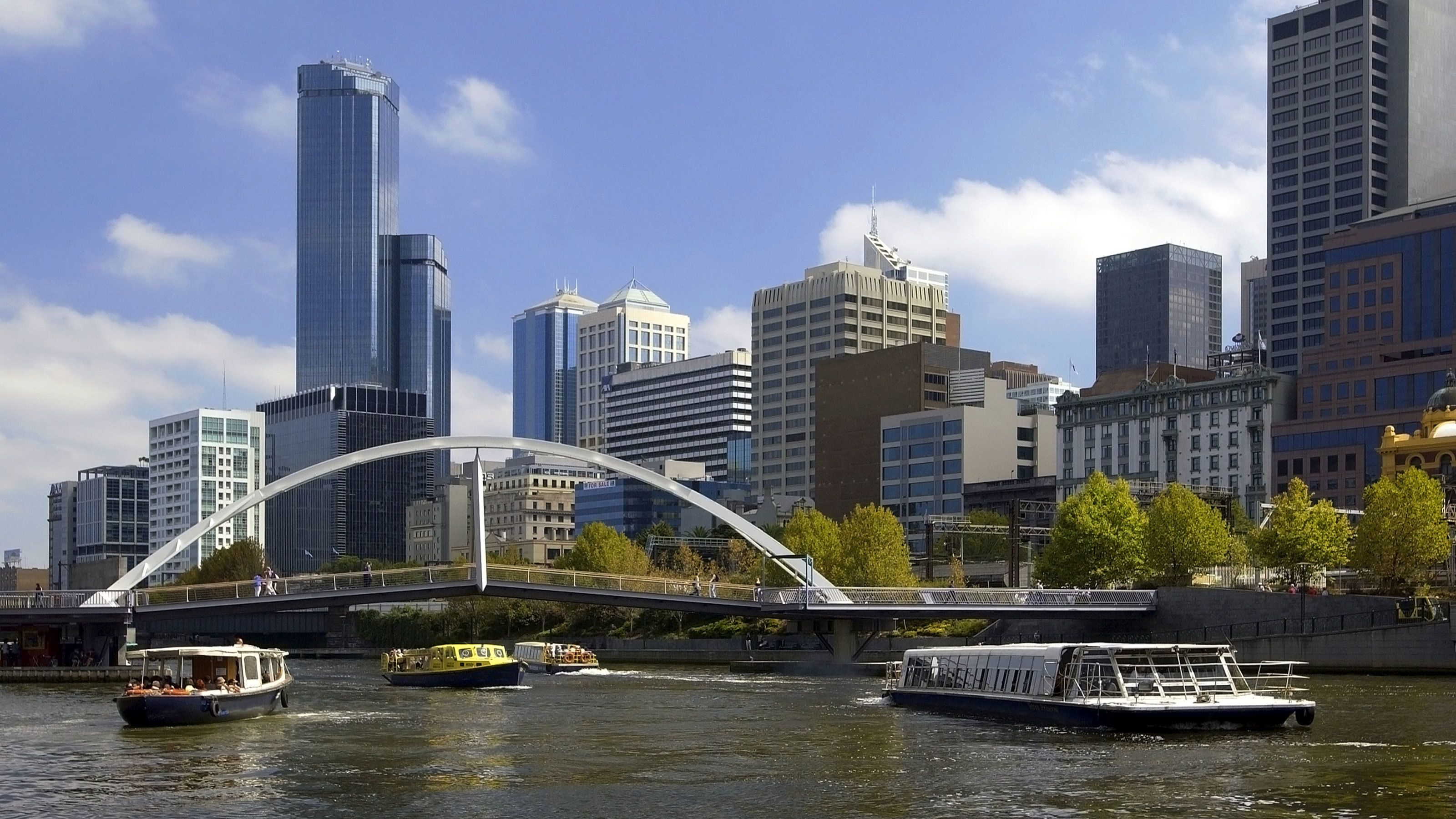 Boats and walking bridge over the Yarro River with city in the background in Melbourne