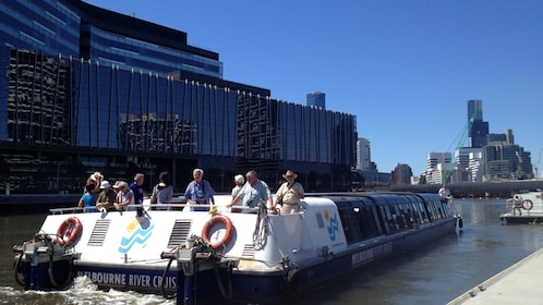 Cruise boat passengers on the upper deck as they go down the Yarra River in Melbourne