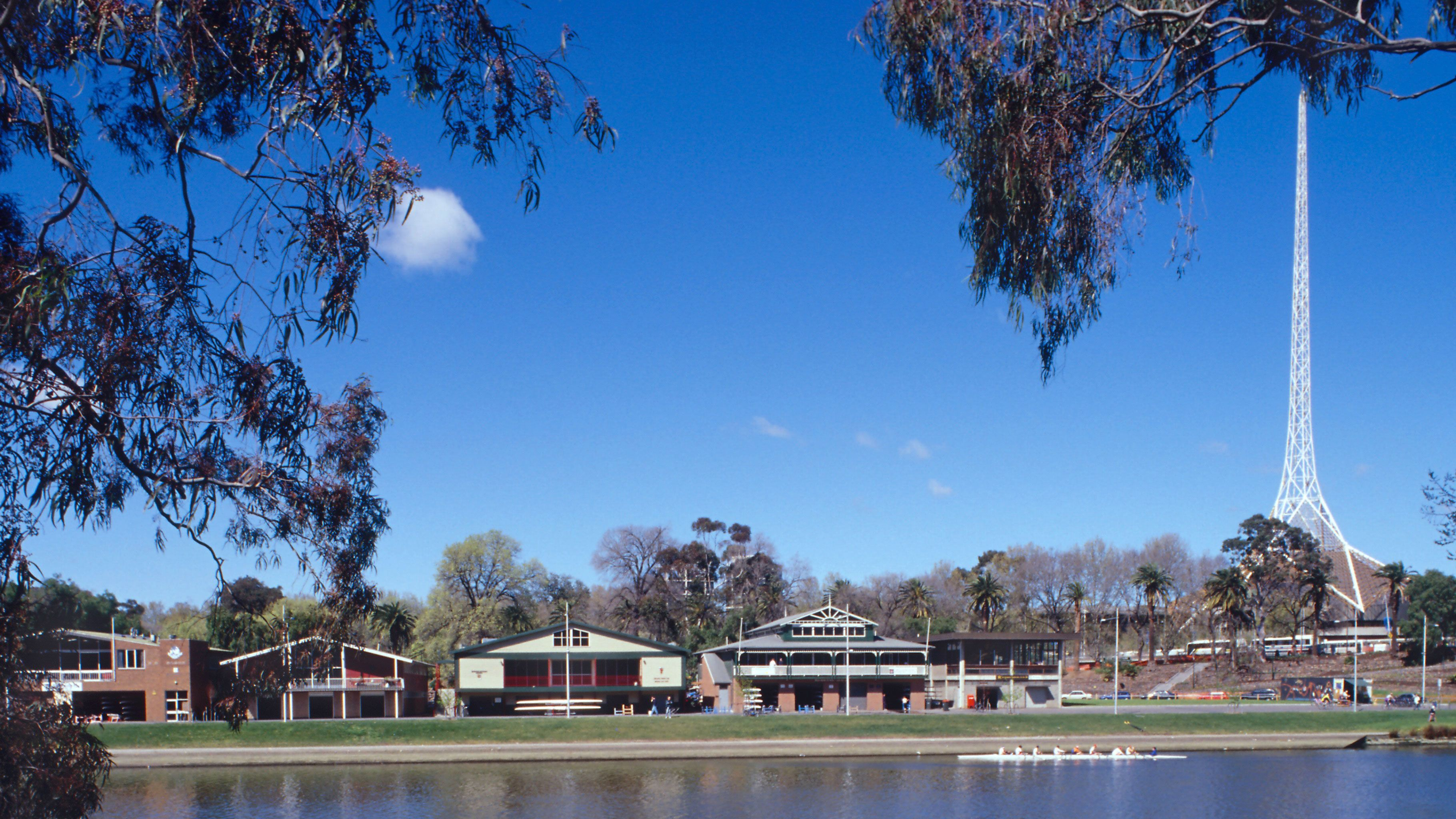 Buildings along the bank of the Yarra River with the Spire of the Arts Centre rising above the trees in Melbourne