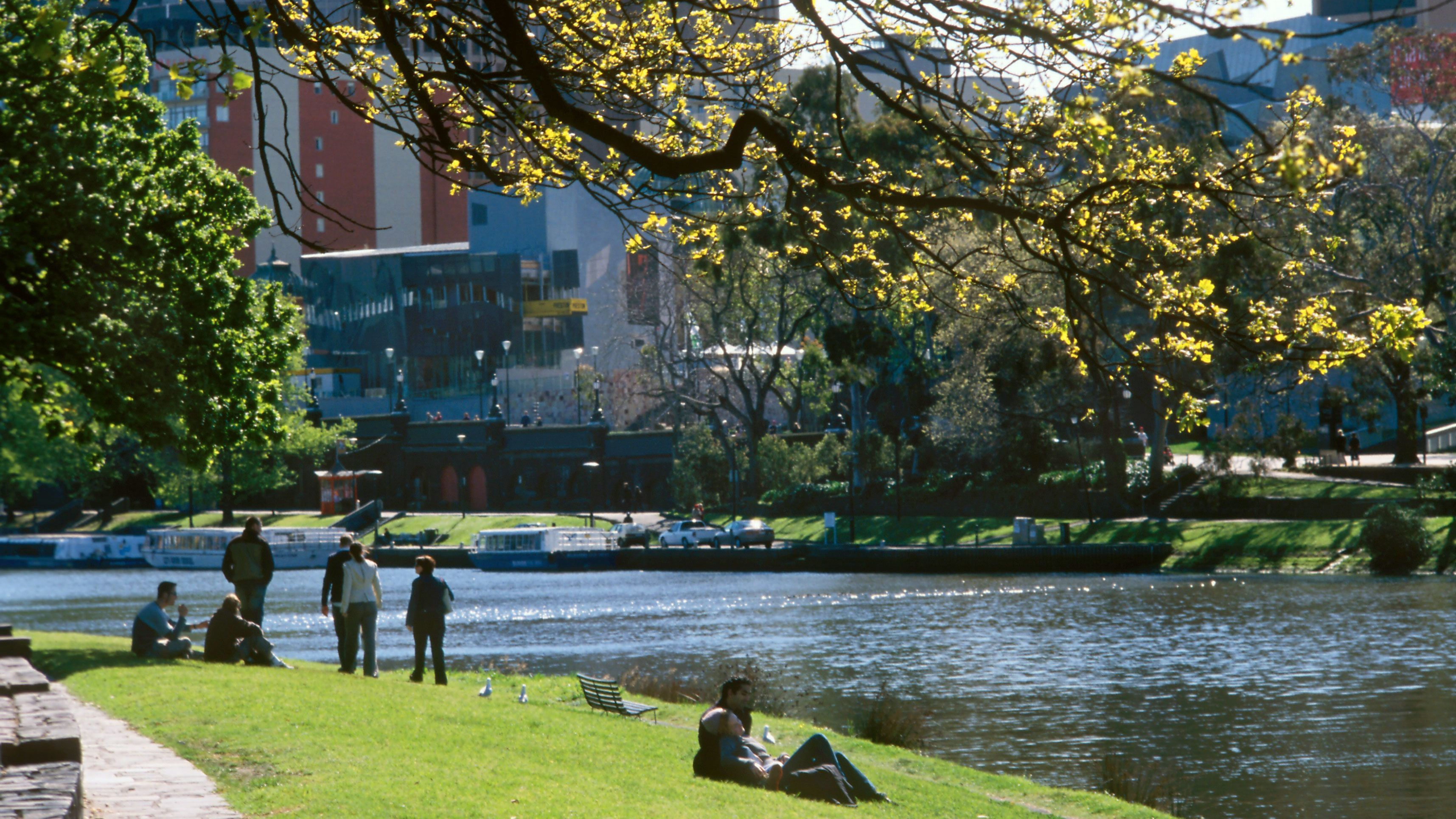 People relax on the grass along the bank of the Yarra River in Melbourne