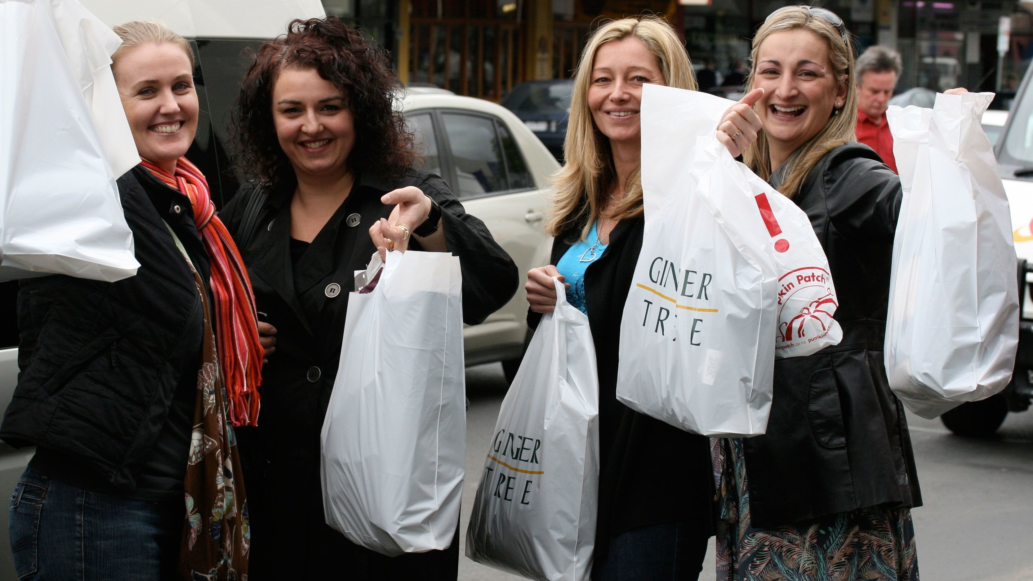 Shopping group holding up bags of purchases in Melbourne
