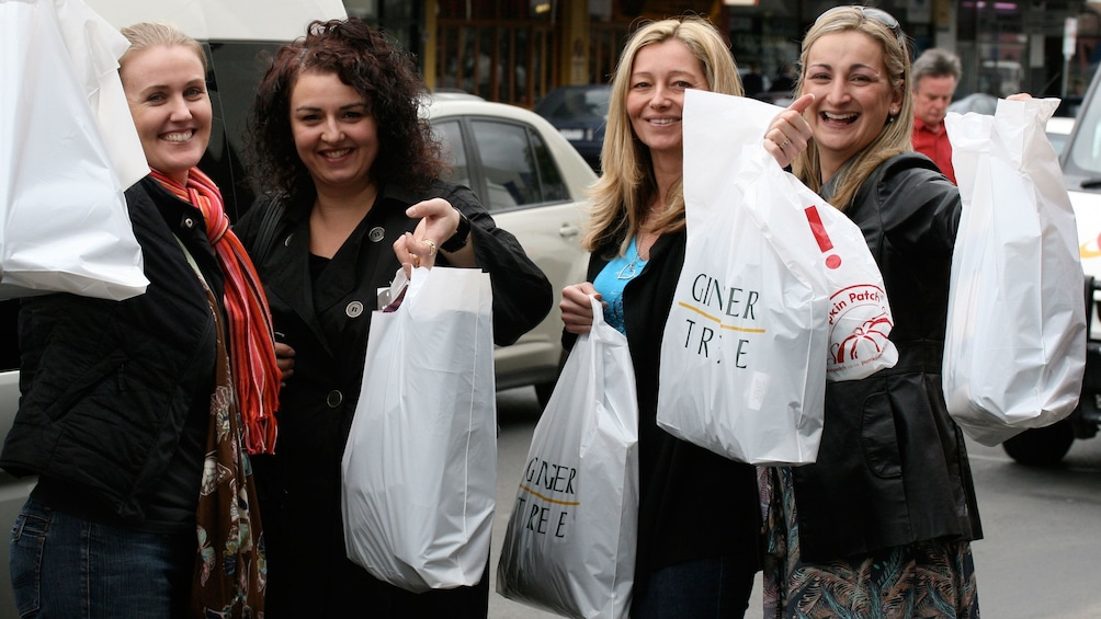 Show item 3 of 6. Shopping group holding up bags of purchases in Melbourne