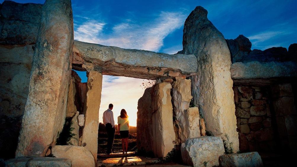 Lataa valokuva 4 kautta 4. couple watching the sunset from the entrance to the prehistoric stone temple in Malta