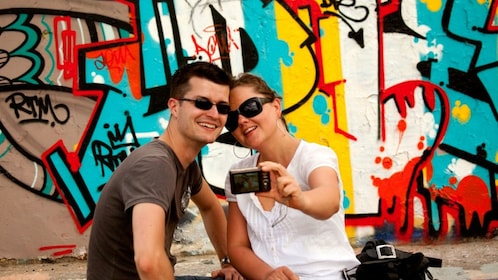 Couple taking picture in front of graffiti in Berlin
