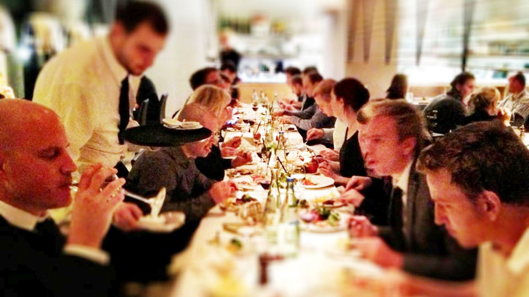 A large group of people sitting at a long table at a restaurant in Berlin
