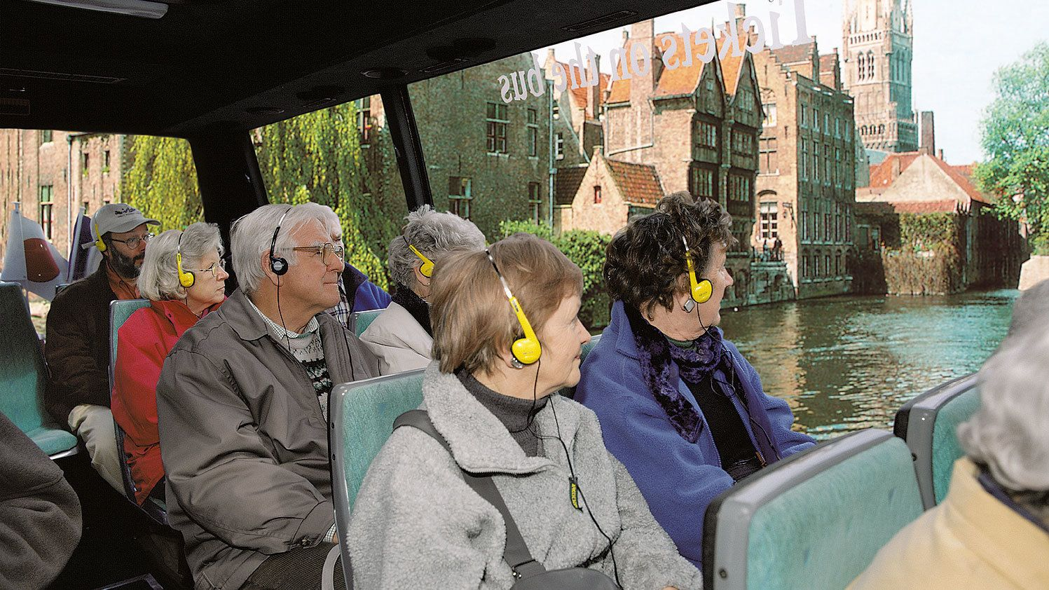 Tourists enjoying a tour aboard the City Tour bus with audio guide headphones on in Bruges